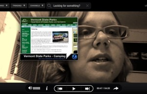 A video closeup of a woman's face. She's wearing glasses, and next to her on-screen is a preview of the Vermont State Parks website.