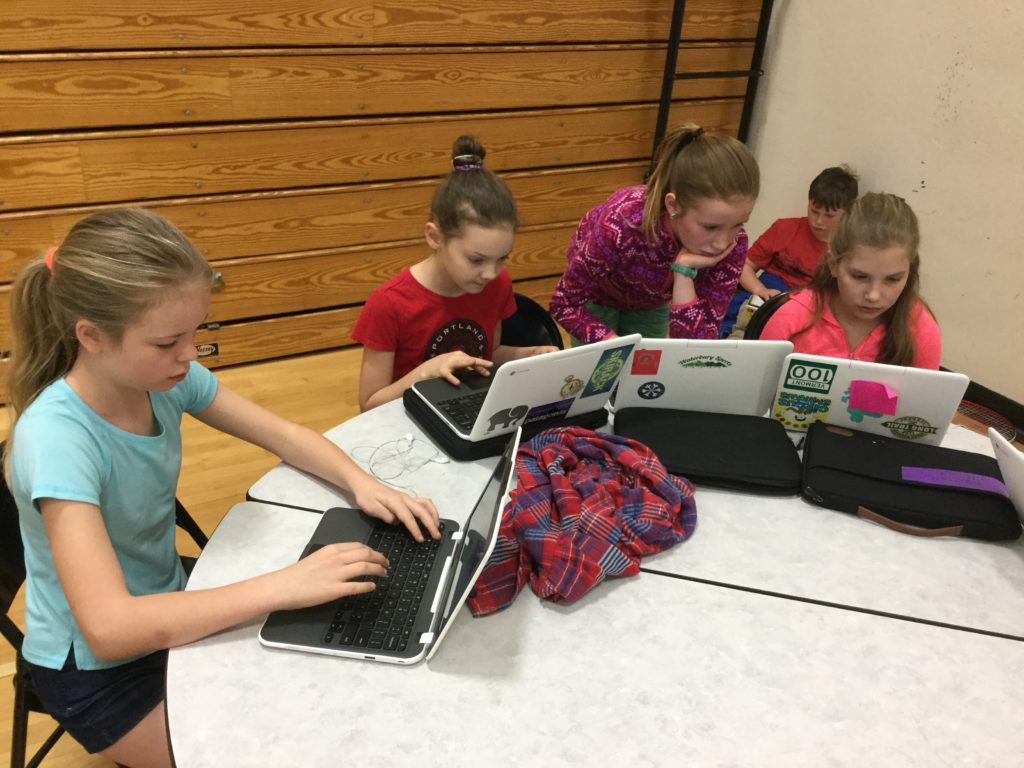 Students typing on laptops.