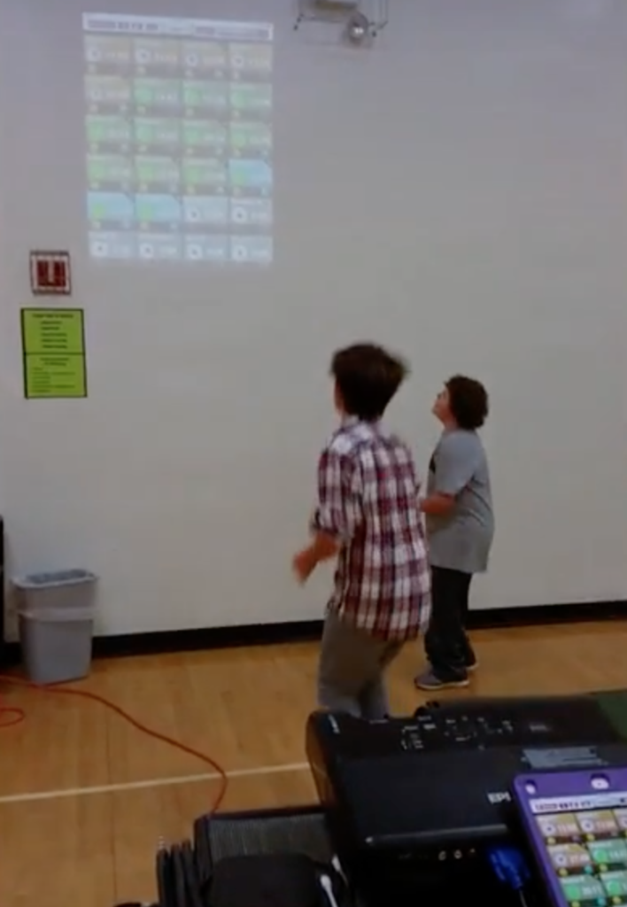 Personalizing phys ed: students watching a projection on the wall.