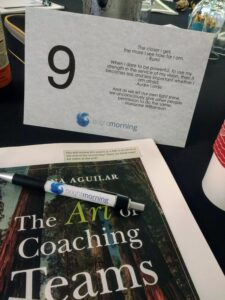 A photo showing a copy of the book 'The Art of Coaching Teams', a pen, and a table tent that includes a quote from Rumi.