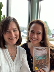 Host Jeanie Phillips, left, with guest Meg Allison, right, and a copy of the book Pride by Ibi Zoboi