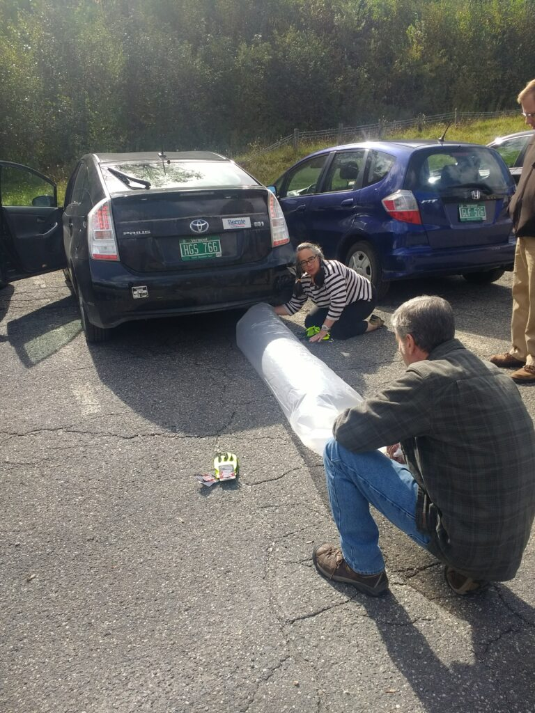 2 adults hold a plastic tube-shaped bag to a car's exhaust pipe, confronting climate change