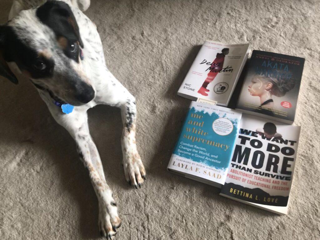 Dog next to four books